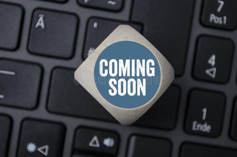 Cube and dice with term coming soon. Cube and dice on laptop keyboard with term coming soon royalty free stock image