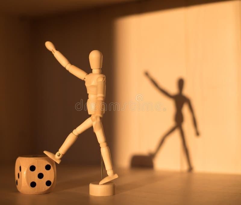 Cube en bois et homme en matrices moulant une ombre Toujours dur?e conceptuelle Abstraction de victoire images stock