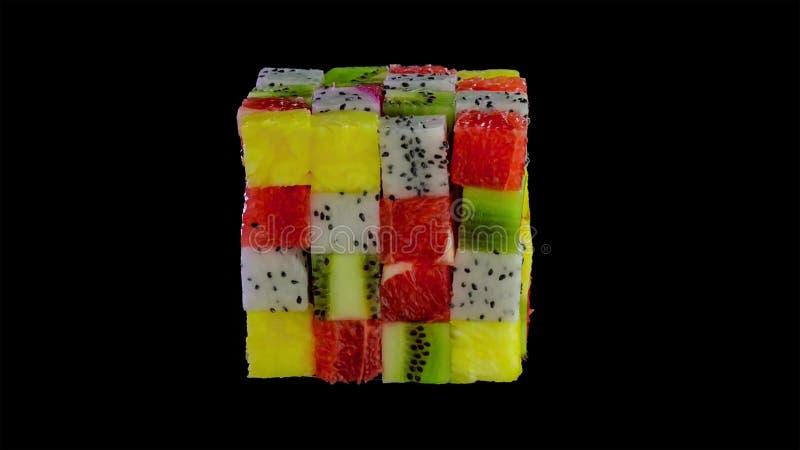Cube en fruit formé de petites places de fruit tropical assorti dans une disposition colorée comprenant le kiwi, fraise, orange photo stock