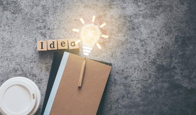 Cube letter word of Idea with notebook, pencil, coffee cup and light bulb with copy space. Futuristic icon photo concept of stock photography
