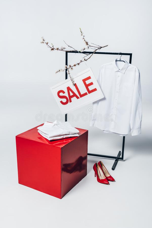 Cube, red high heels, shirt on hanger and sale sign, summer. Sale concept royalty free stock photo