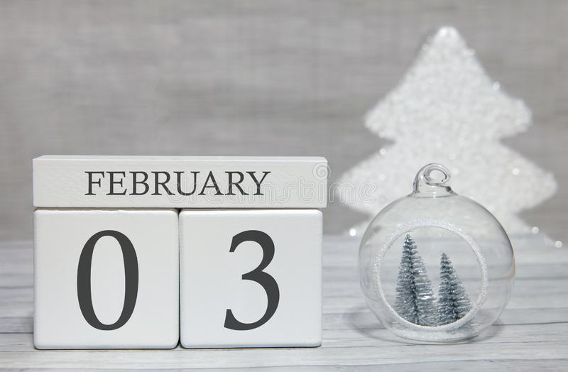 Cube shape calendar for February 3 on wooden surface and light background with empty space for text stock image
