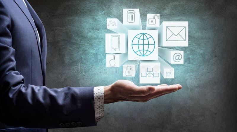 Cubes actuels en homme d'affaires avec des icônes en main images stock