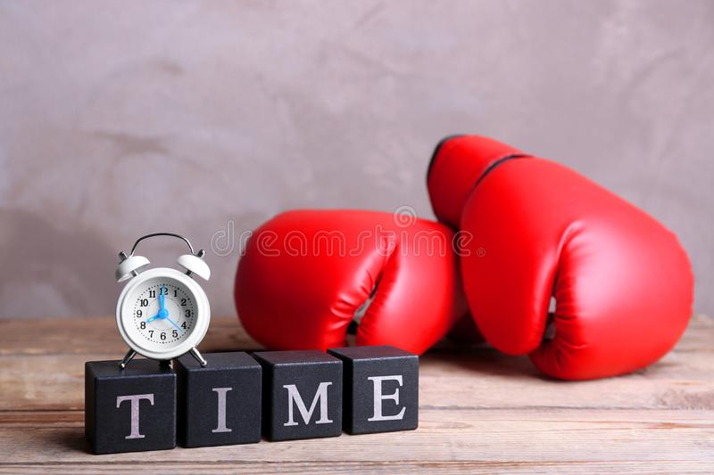 Cubes with alarm clock and boxing gloves on wooden table royalty free stock photos