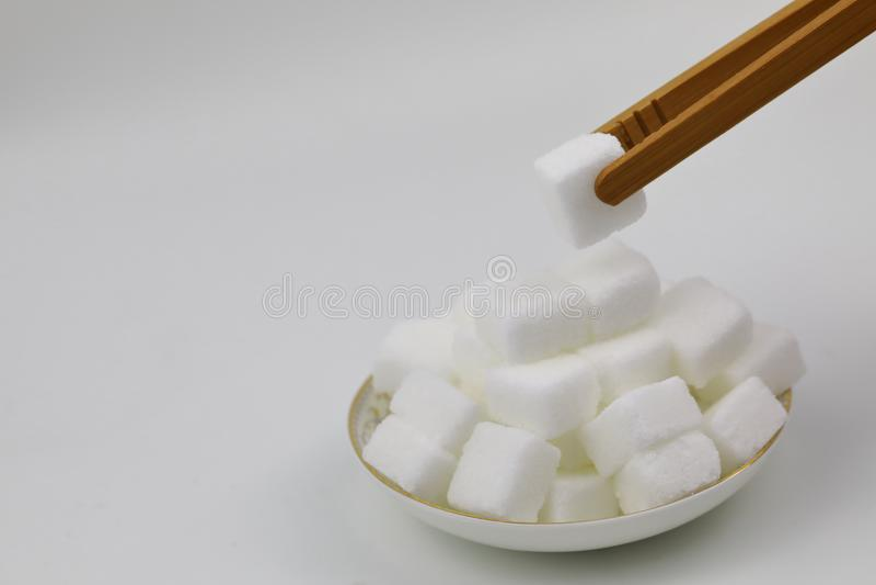 Cubes blancs en sucre de roche sur un dessert de table de nourriture de plat sur la montre haute de fin blanche de fond hors du d photographie stock libre de droits