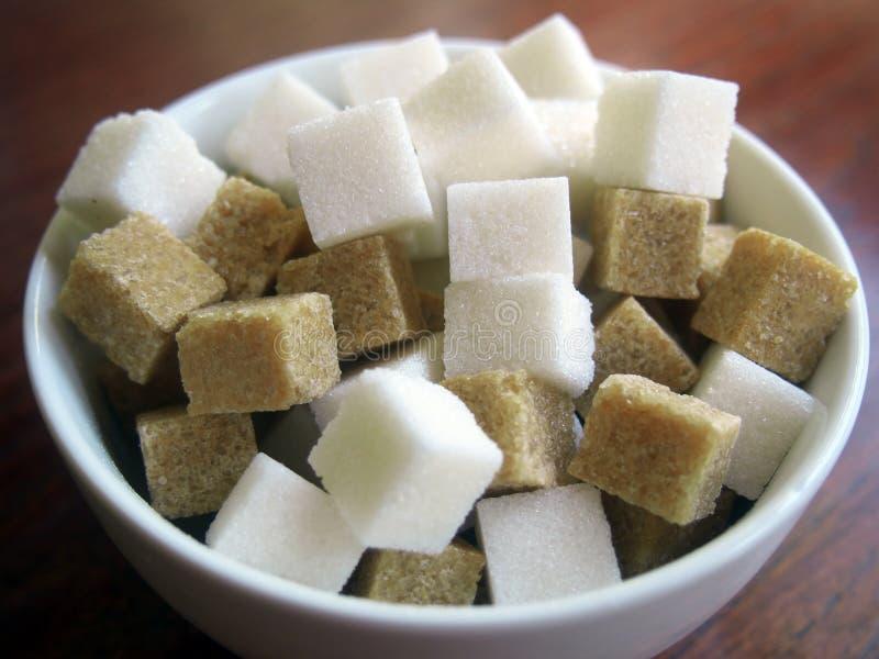 Cubes de blanc et de sucre roux dans une cuvette en céramique image stock