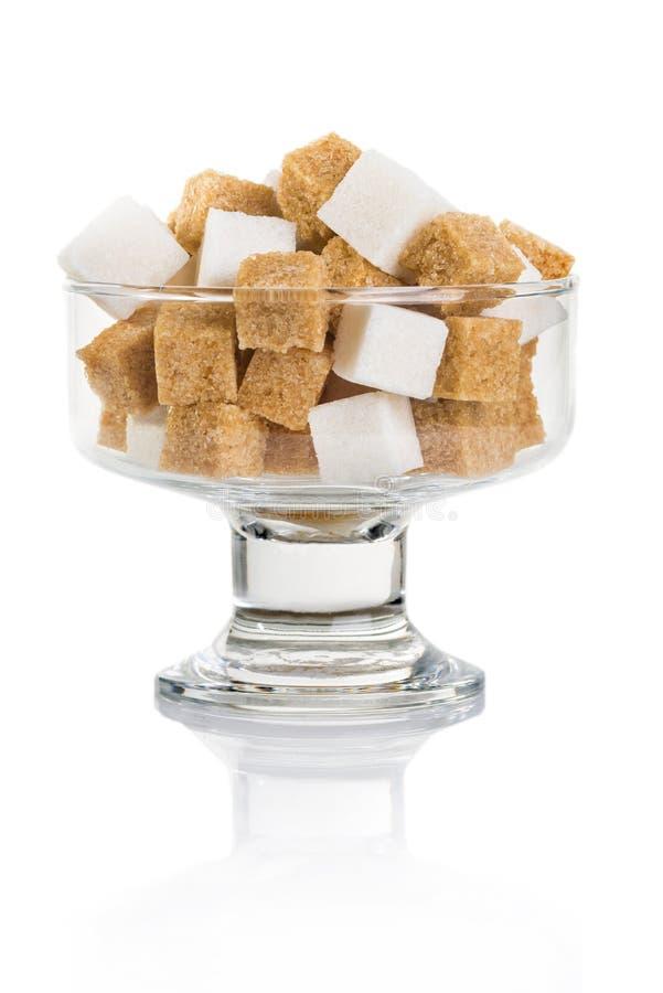 Cubes de sucre brun et blanc dans un vase en verre image stock
