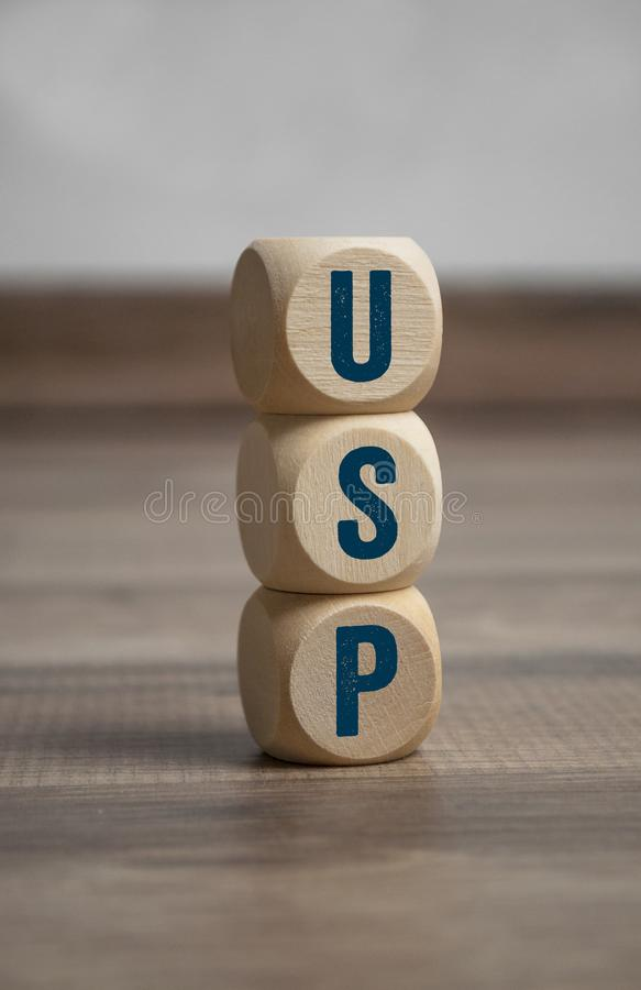 Cubes and dice with acronym USP unique selling proposition or unique selling point. On wooden background stock photography
