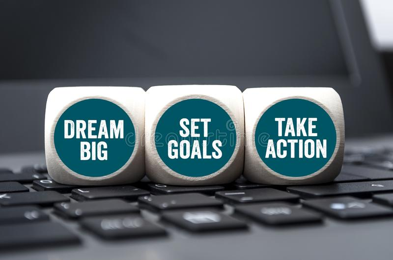 Cubes and dice with dream big, set goals and take action royalty free stock photography