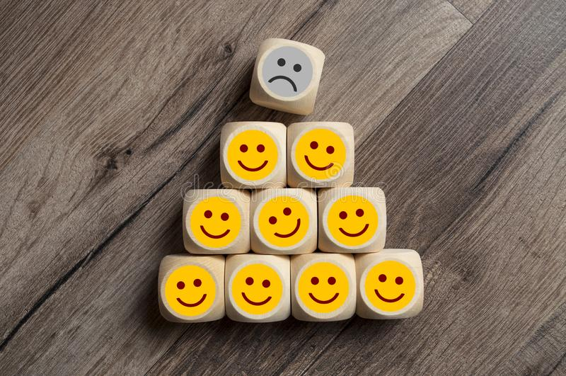 Emoticons with happy, unhappy faces. Cubes dice with Emoticons with happy, unhappy faces on wooden background stock photos