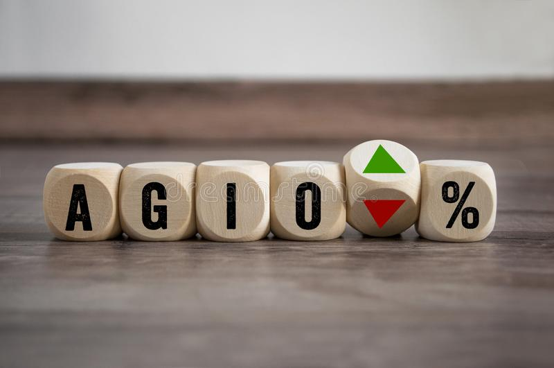 Cubes and dice with the financial term AGIO. On wooden background stock photos