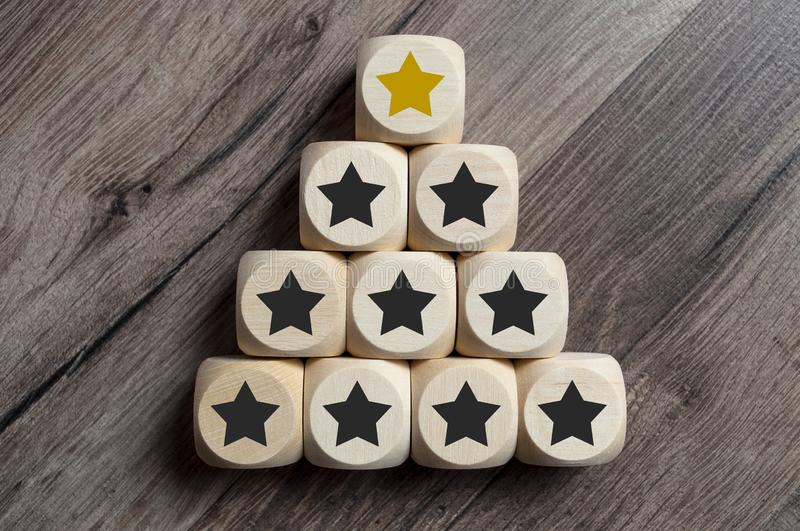 Cubes and dice with golden star on top of a pyramide. On wooden background royalty free stock photo