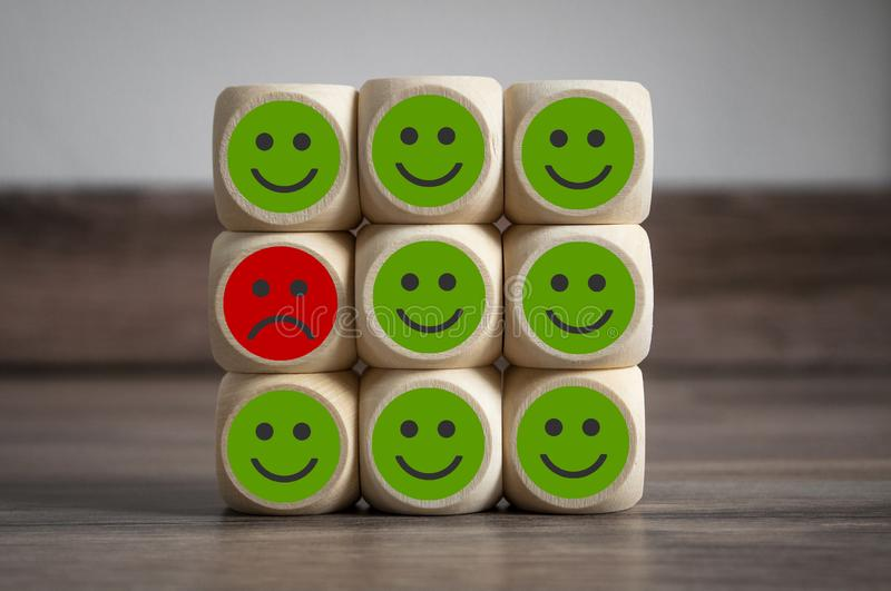 Cubes and dice with green and red smileys metaphor for customer service poll or termination cancellation. On wooden background stock images