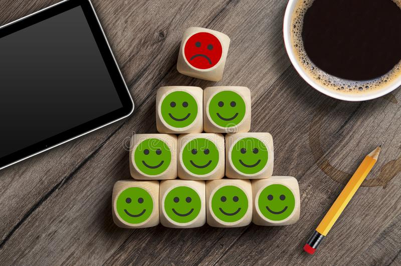 Cubes and dice with green and red smileys metaphor for customer service poll or termination cancellation. On wooden background royalty free stock photography