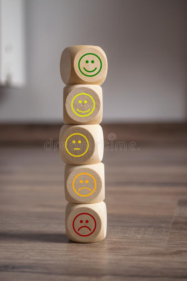 Cubes, dice and paper work with rating emoticons. On wooden background royalty free stock photo