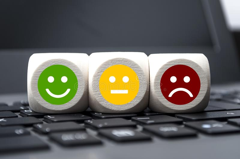 Cubes dice and paper work with rating emoticons for customer support. Cubes dice and paperwork with rating emoticons for customer support royalty free stock photography