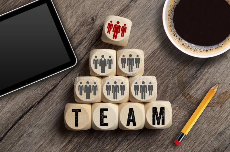 Cubes and dice showing TEAM on a workplace with tablet and cup of coffee royalty free stock images