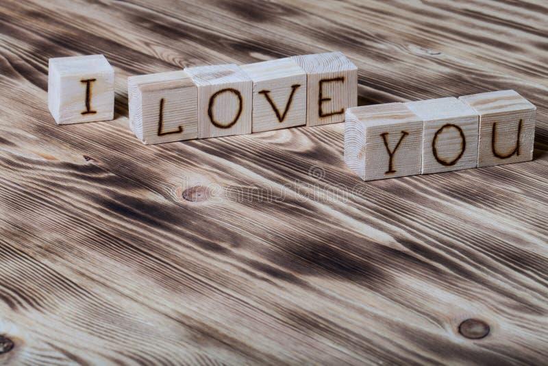 Cubes en bois avec l'inscription JE T'AIME sur le nouveau fond en bois photos stock