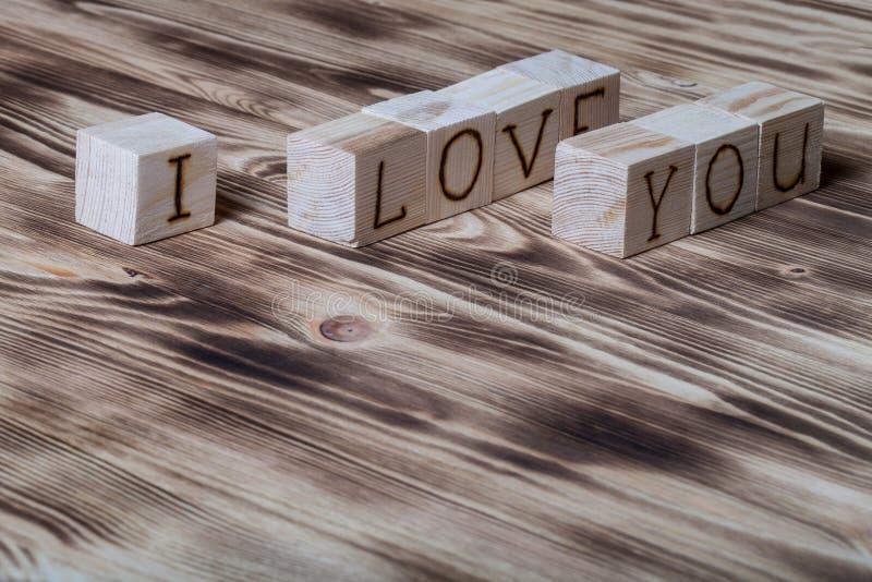 Cubes en bois avec l'inscription JE T'AIME sur le nouveau fond en bois photo libre de droits