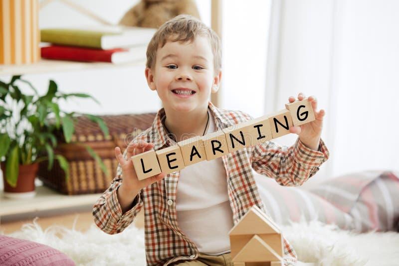 Cubes en bois avec le mot APPRENANT dans des mains de peu de garçon image stock