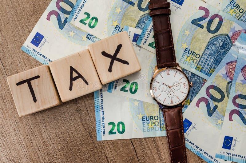 Cubes en bois en impôts avec l'horloge sur l'euro photographie stock libre de droits