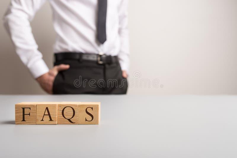Cubes en bois orthographiant des FAQ photos stock