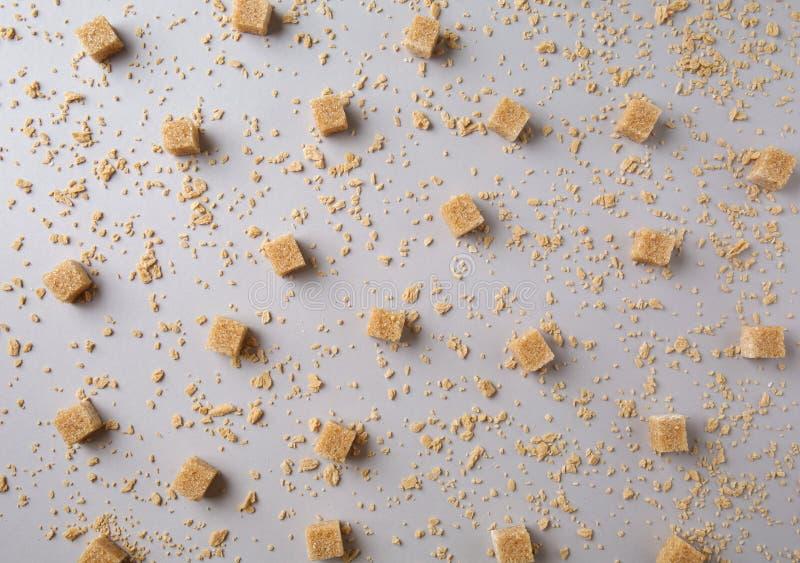 Cubes en Brown avec des flocons de sucre d'érable sur le fond gris photos stock