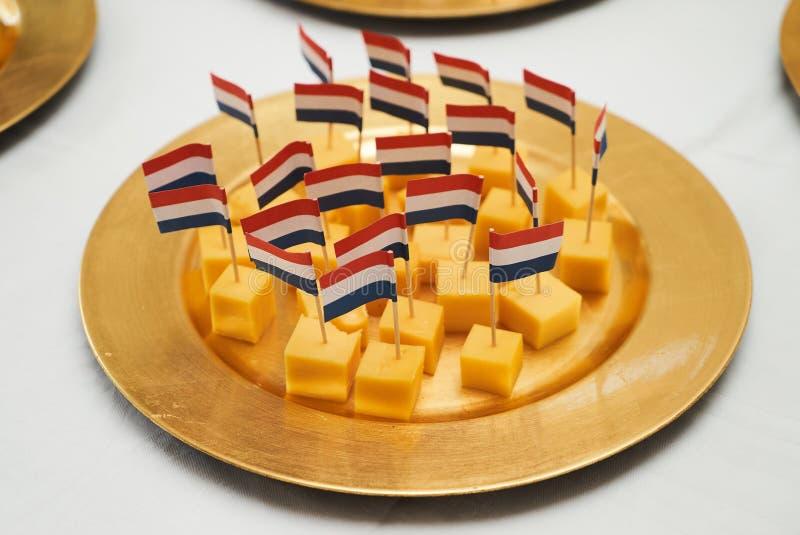 Cubes en fromage de Hollande avec des drapeaux images stock