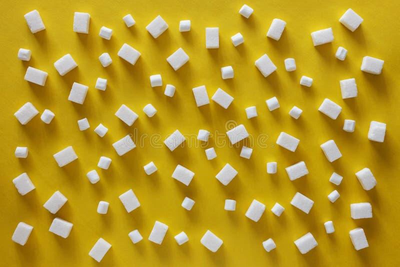 Cubes et guimauves en sucre sur le fond jaune photos stock