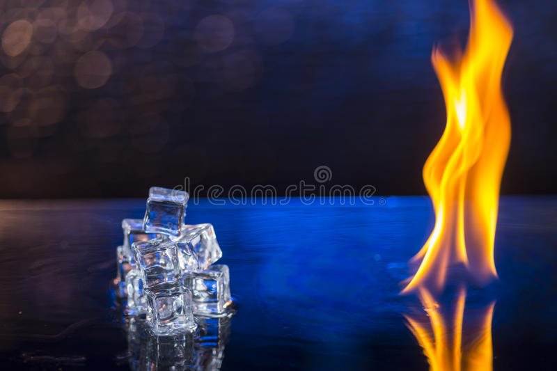 cubes of ice and fire on a water surface on an abstract background stock image