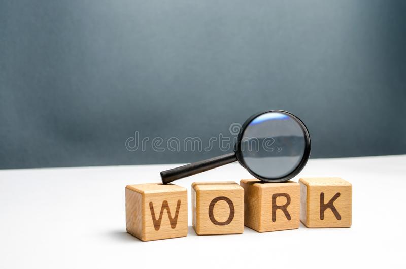 Cubes labeled work and magnifying glass. Concept of job search or workers. Human resources, hiring specialists and specialized royalty free stock photo