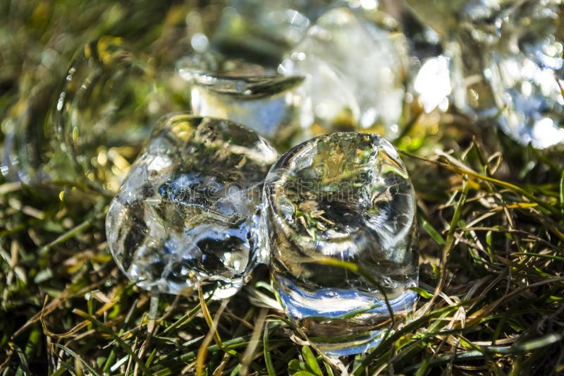 Cubes of large ice lie on a green summer grass. Play of color and patches of light. Background or texture. Cubes of large ice lie on a green summer grass. Play stock photos