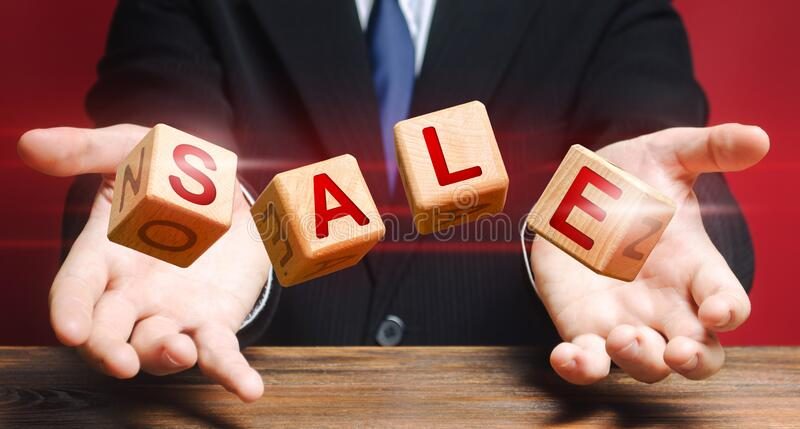 Cubes thrown by a man make up word Sale. Big sale and high discounts on goods. Shopping event. Promotions attracting customers stock photography