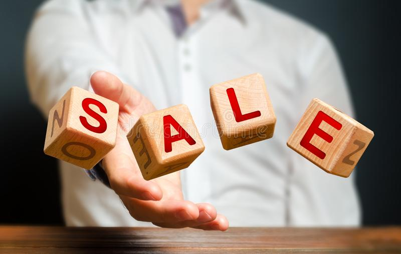 Cubes thrown by a man make up the word Sale. Big sale and high discounts on goods. Promotions and advertising, attracting stock image