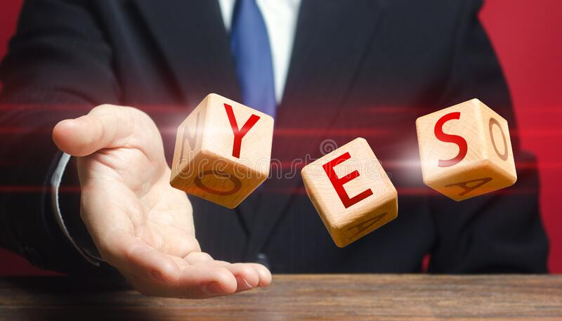 Cubes thrown by a man make up word YES. Agreement and acceptance, answer the question. Confirmation and approval. Important stock photo