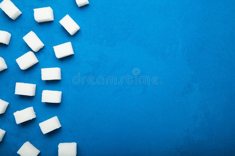 Cubes of white sugar on a blue vintage background, concept. Copy space.  stock image