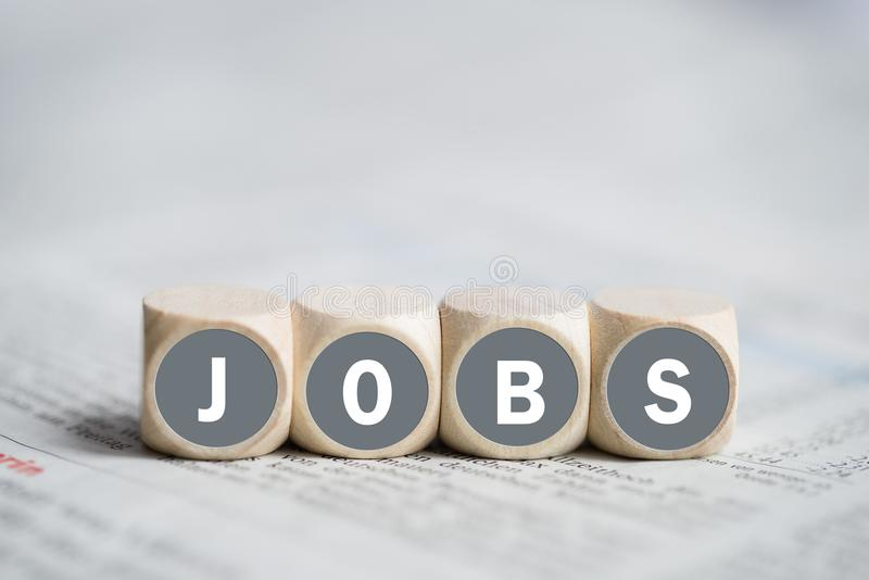 Cubes with the word `JOBS`. On a newspaper royalty free stock photos