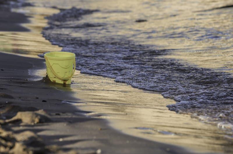 A cubeta amarela da criança na praia foto de stock