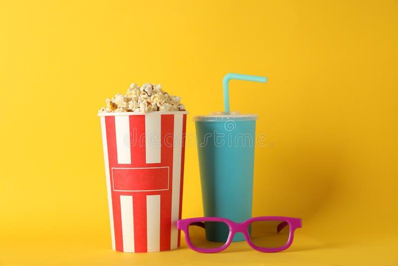 Cubeta com pipoca, bebida e vidros 3d no fundo amarelo fotografia de stock
