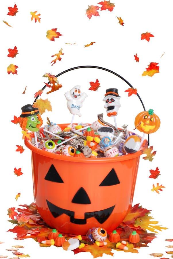 Cubeta da abóbora de Halloween com as folhas da queda dos doces fotos de stock royalty free