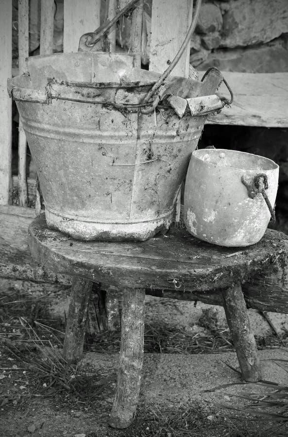 Cubeta da lata e um potenciômetro de alumínio sobre o tamborete do estábulo velho fotos de stock