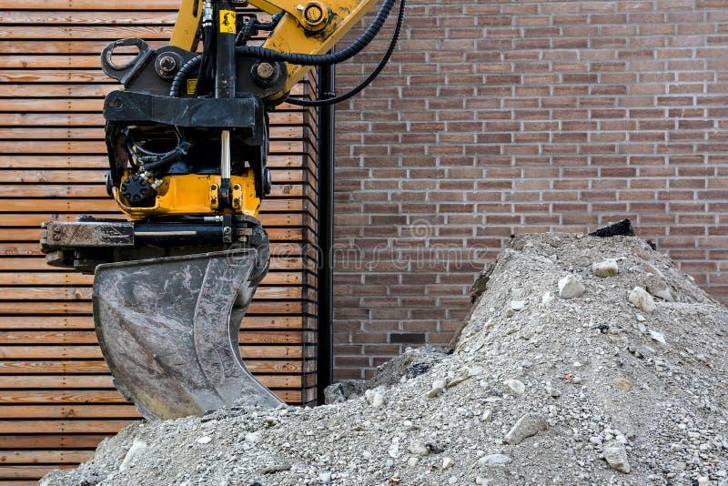 Cubeta da máquina escavadora em um montão do cascalho na perspectiva de uma parede de tijolo imagens de stock
