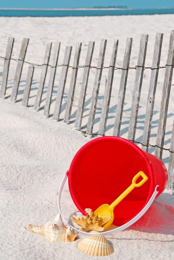 Cubeta da praia pela cerca fotografia de stock