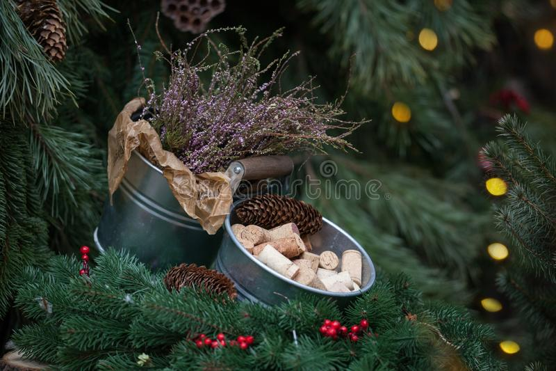 Cubeta decorativa de cortiça do vinho Festão do ramo de árvore do Natal com cones do pinho e Holly Berries vermelha foto de stock royalty free
