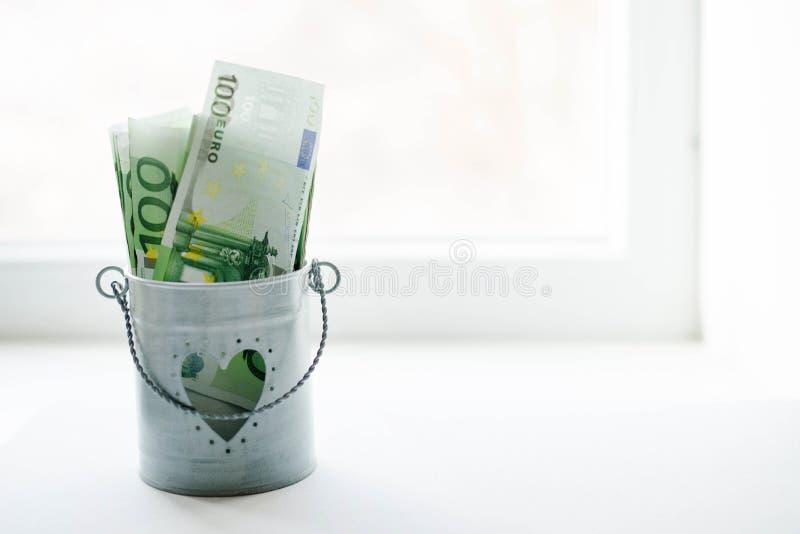 Cubeta enchida com os lotes do euro do dinheiro isolados no fundo branco fotografia de stock royalty free