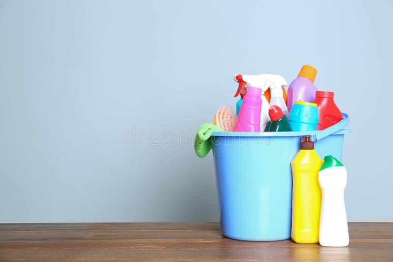 Cubeta plástica com os produtos de limpeza diferentes na tabela contra o fundo da cor foto de stock