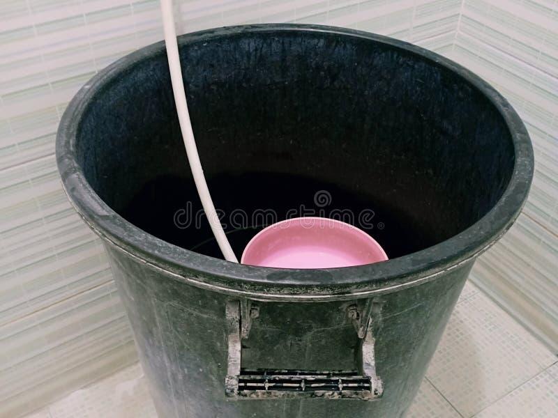 Cubeta plástica preta velha suja da água no banheiro foto de stock royalty free