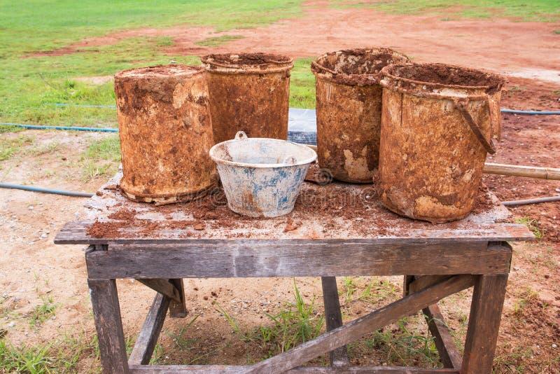 Cubeta suja velha para a constru??o no fundo de madeira da tabela fotografia de stock