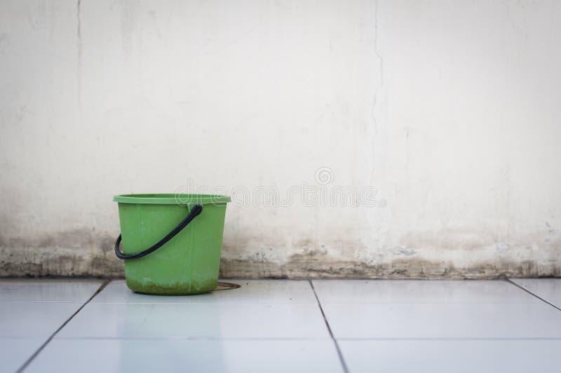 Cubeta verde da água no assoalho telhado e no fundo concreto velho foto de stock royalty free