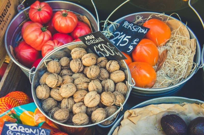 Cubetas completas das porcas, dos caquis, dos tomates e das outras frutas e legumes em um mercado local em Girona imagem de stock royalty free